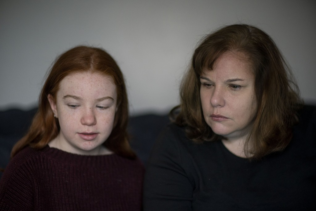 Eileen Carroll, right, sits with her daughter, Lily, 11, as she attends school remotely from their home in Warwick, R.I, Wednesday, Dec. 16, 2020. Whe...