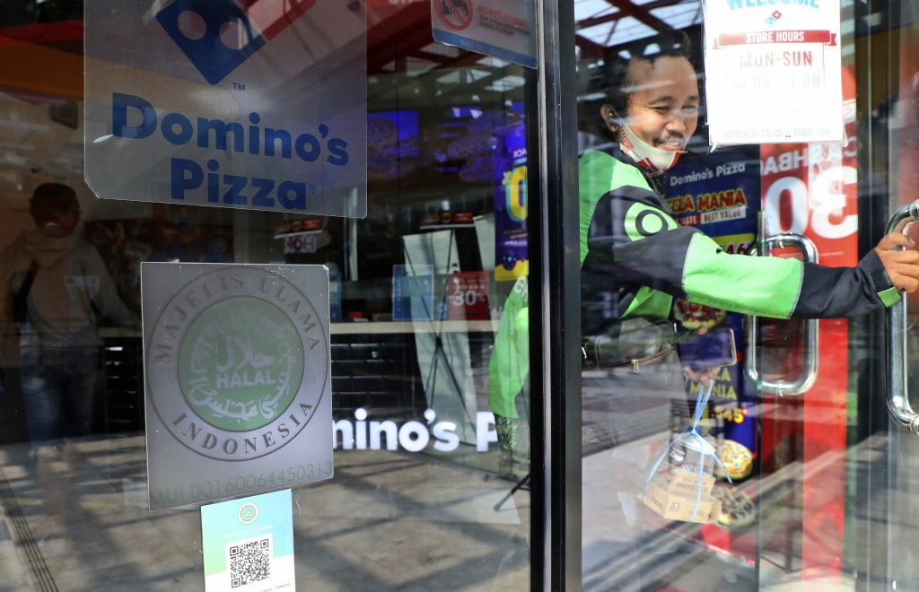 A man leaves as 'halal' logo of Indonesian Ulema Council is displayed on the facade of a restaurant in Jakarta, Indonesia, Wednesday, Nov. 11, 2020. A...