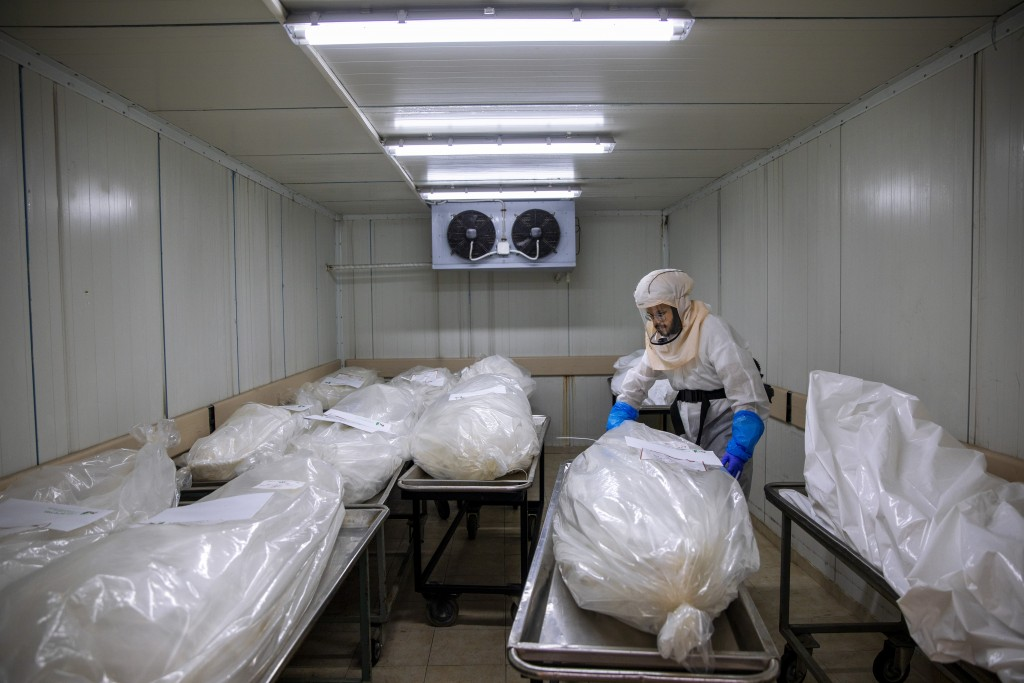 "A worker from ""Hevra Kadisha,"" Israel's official Jewish burial society, prepares bodies before a funeral procession at a special morgue for COVID-19 v..."