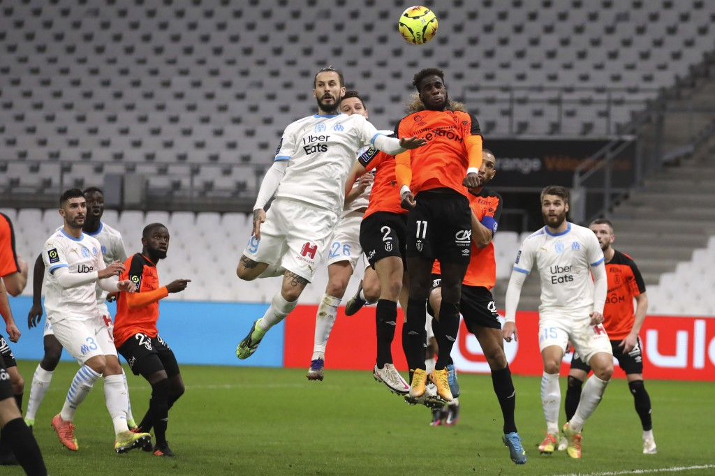 Marseille's Dario Benedetto, left, Marseille's Florian Thauvin, second left, jumps for the ball with Rennes' M'Baye Niang, right, during the French Le...