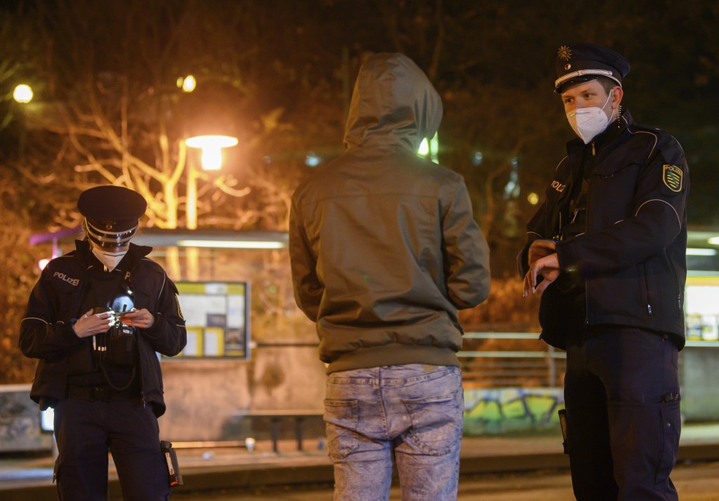 Police officers talk to a man during a curfew check at night in the Gorbitz district in Dresden, Germany, Saturday, Dec. 19, 2020. A hard lockdown has...