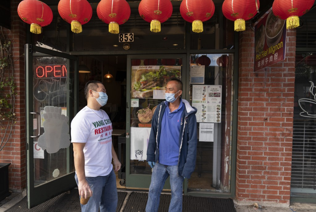 Benny Yun, owner of Yang Chow restaurant, left, talks to a fellow cafe owner Michael H., in Los Angeles, Thursday, Dec. 17, 2020. Bigotry toward Asian...