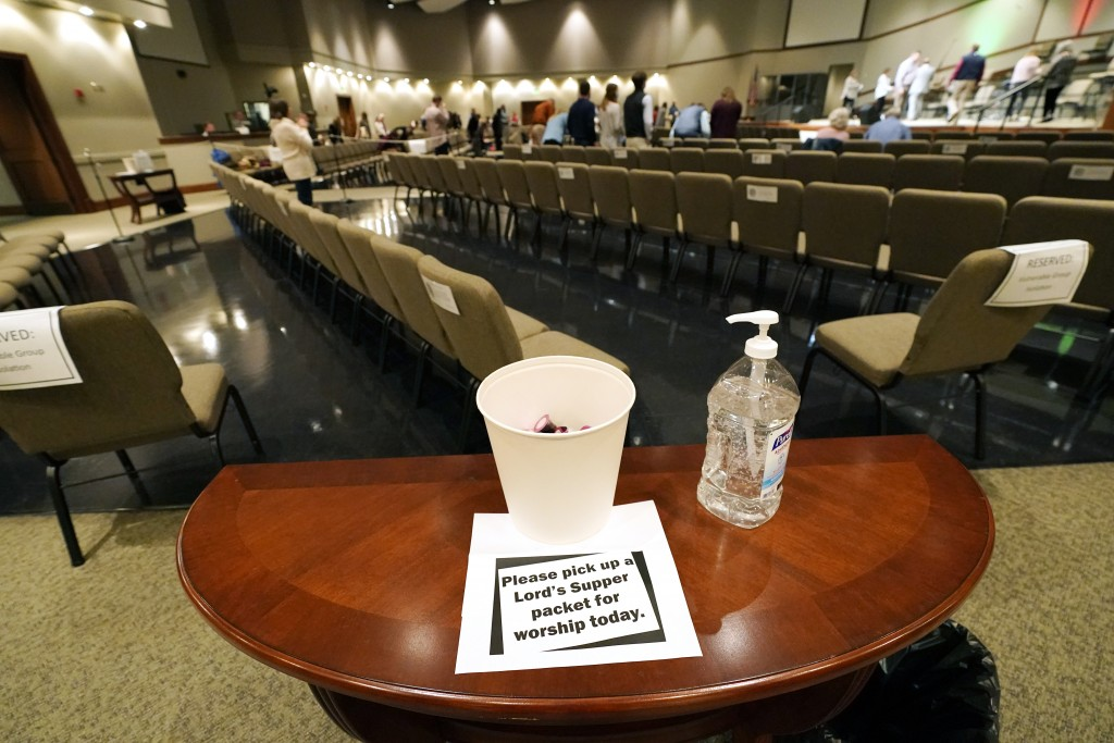 Congregants of Highland Colony Baptist Church are encouraged to spritz their hands with sanitizer before picking up a communion packet, while having a...