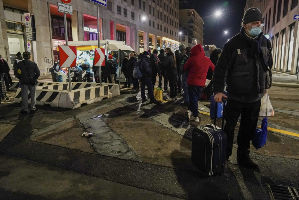 Giovanni Petazzi stands with his trolley as he queues for a free meal at the Progetto Arca food truck in downtown Milan, Italy, Thursday, Dec. 10, 202...