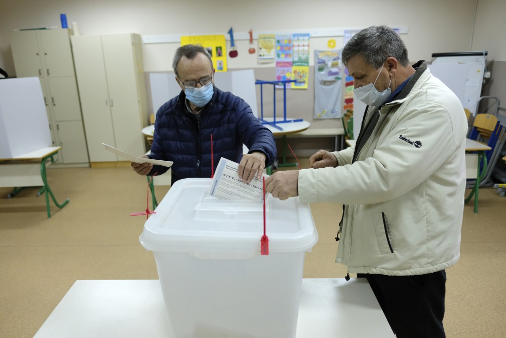 A man casts his ballot for the local elections at a polling station in Mostar, Bosnia, Sunday, Dec. 20, 2020. Divided between Muslim Bosniaks and Cath...