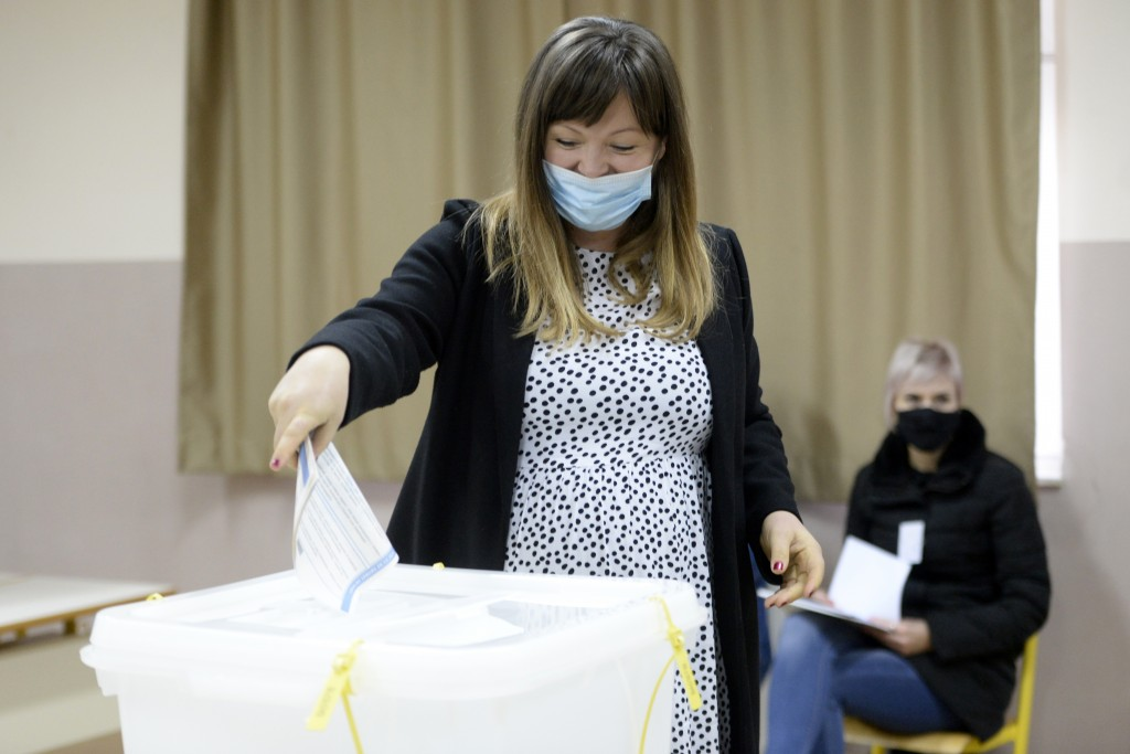 Irma Baralija casts her ballot for the local elections at a polling station in Mostar, Bosnia, Sunday, Dec. 20, 2020. Baralija hopes to win her race a...