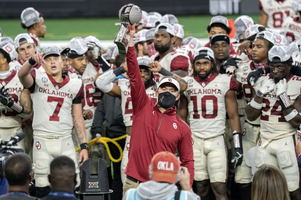 Oklahoma head coach Lincoln Riley hosts the Big 12 Conference championship trophy after defeating Iowa State 27-21 in an NCAA college football game, S...