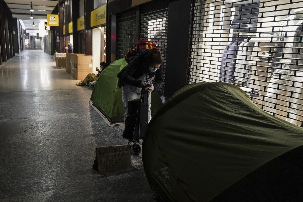 Progetto Arca Onlus' nurse Clelia, visits the homeless who have set up tents for the night under an arcade in downtown Milan, northern Italy, Friday, ...