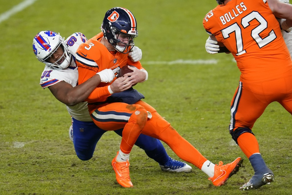 Denver Broncos quarterback Drew Lock is hauled down for a sack by Buffalo Bills defensive tackle Ed Oliver during the second half of an NFL football g...