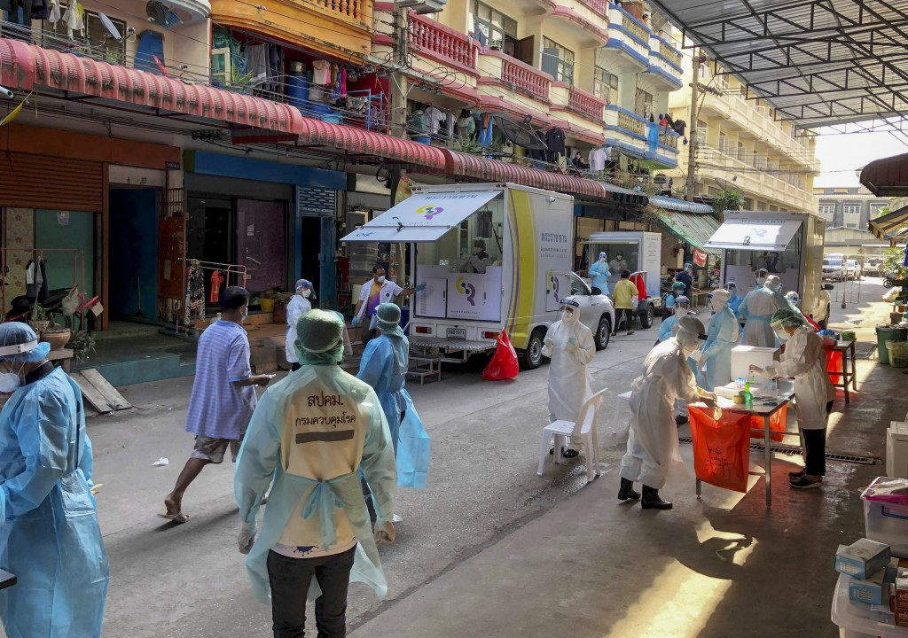 Health workers in protective clothing conduct screening for COVID-19 in Samut Sakhon, south of Bangkok, Thailand, Sunday, Dec. 20, 2020. Thailand repo...