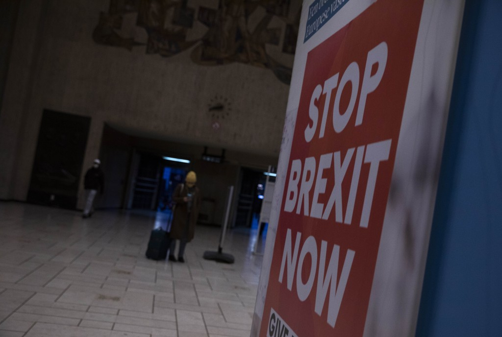 Passengers walk near a banner from the anti-Brexit campaign in Brussels, Sunday, Dec. 20, 2020. The EU and the United Kingdom were still working Sunda...