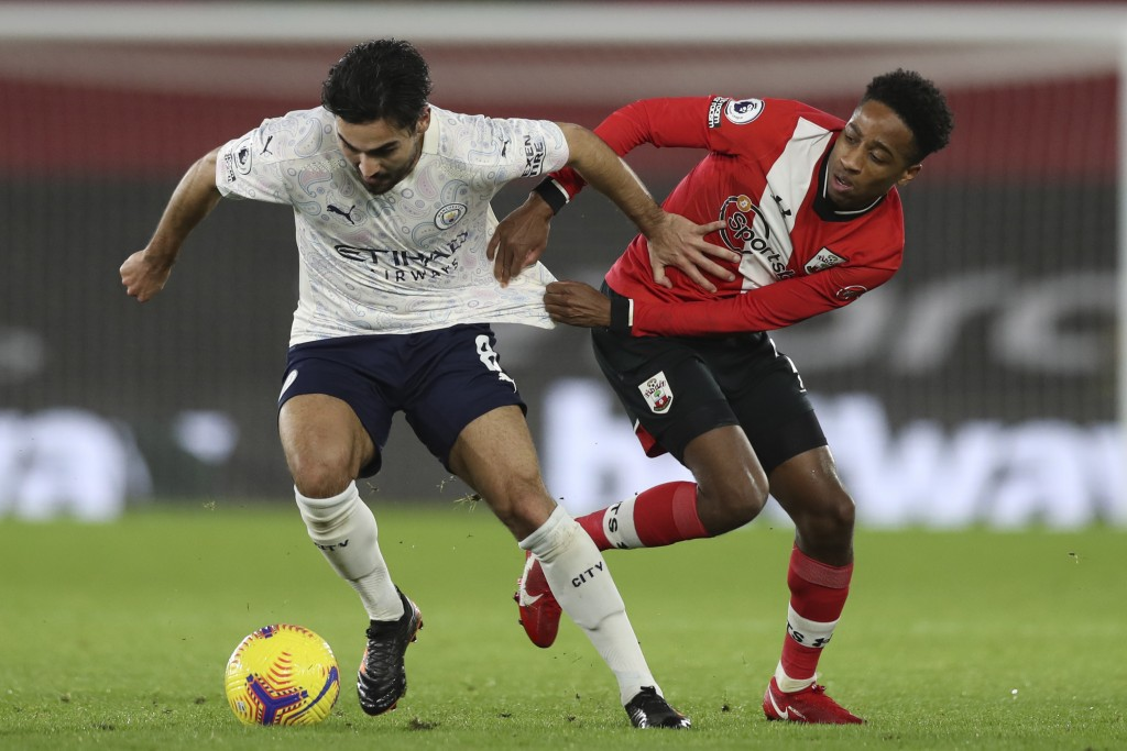Manchester City's Ilkay Gundogan, left, and Southampton's Kyle Walker-Peters vie for the ball during the English Premier League soccer match between S...