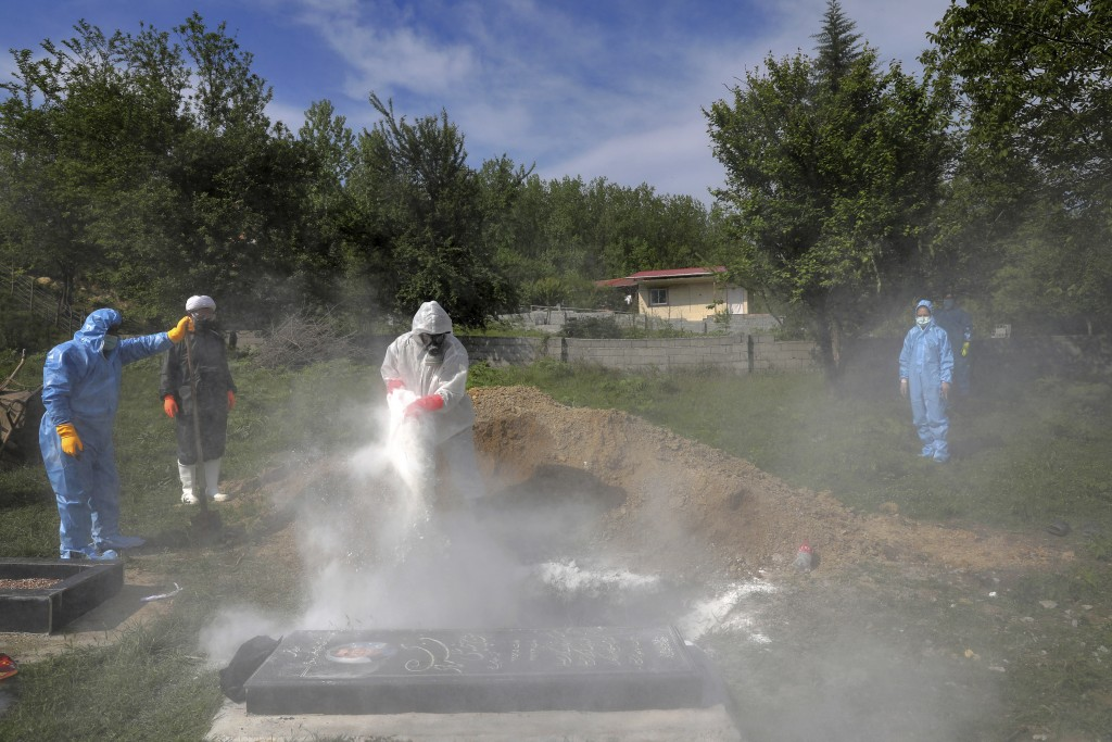 People wearing protective clothing attend the funeral of a victim who died from the coronavirus, at a cemetery in the outskirts of the city of Ghaemsh...