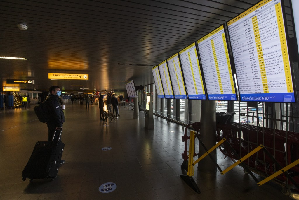 FILE- In this Friday Dec. 18, 2020, file photo, A traveller wearing a face mask checks the flight departures at Schiphol Airport, near Amsterdam, Neth...