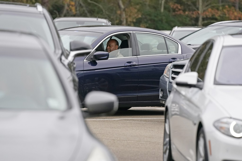 Anderson United Methodist Church member Robert Johnson sits in his car in the church's parking lot and listens as senior pastor Rev. Joe May delivers ...
