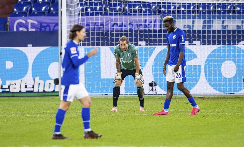 Schalke's Salif Sane , goalkeeper Ralf Faerhrmann and  Benjamin Stambouli  , from right, stand on the pitch disappointed after receiving the opening g...