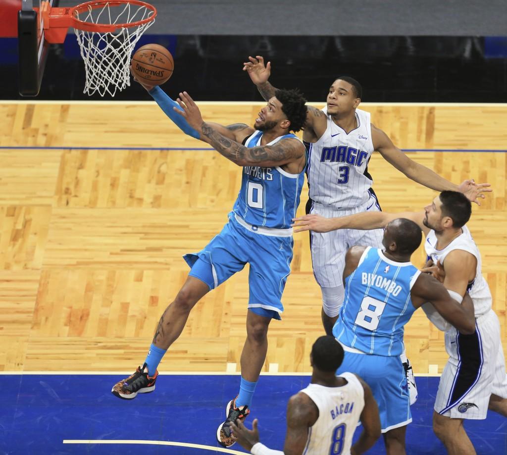 Charlotte Hornets forward Miles Bridges (0) shoots past Orlando Magic forward Chuma Okeke (3) during the second half of an NBA basketball game, Saturd...