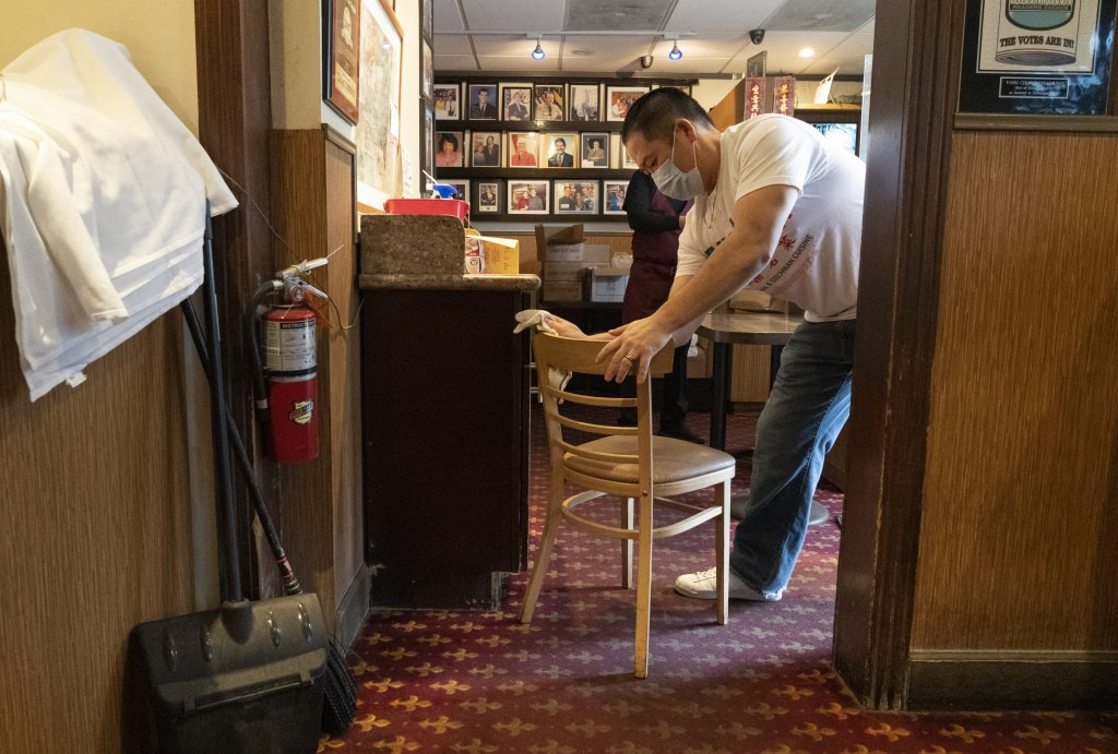 Benny Yun, owner of Yang Chow restaurant sanitizes a chair in Los Angeles, Thursday, Dec. 17, 2020. Bigotry toward Asian Americans and Asian food has ...