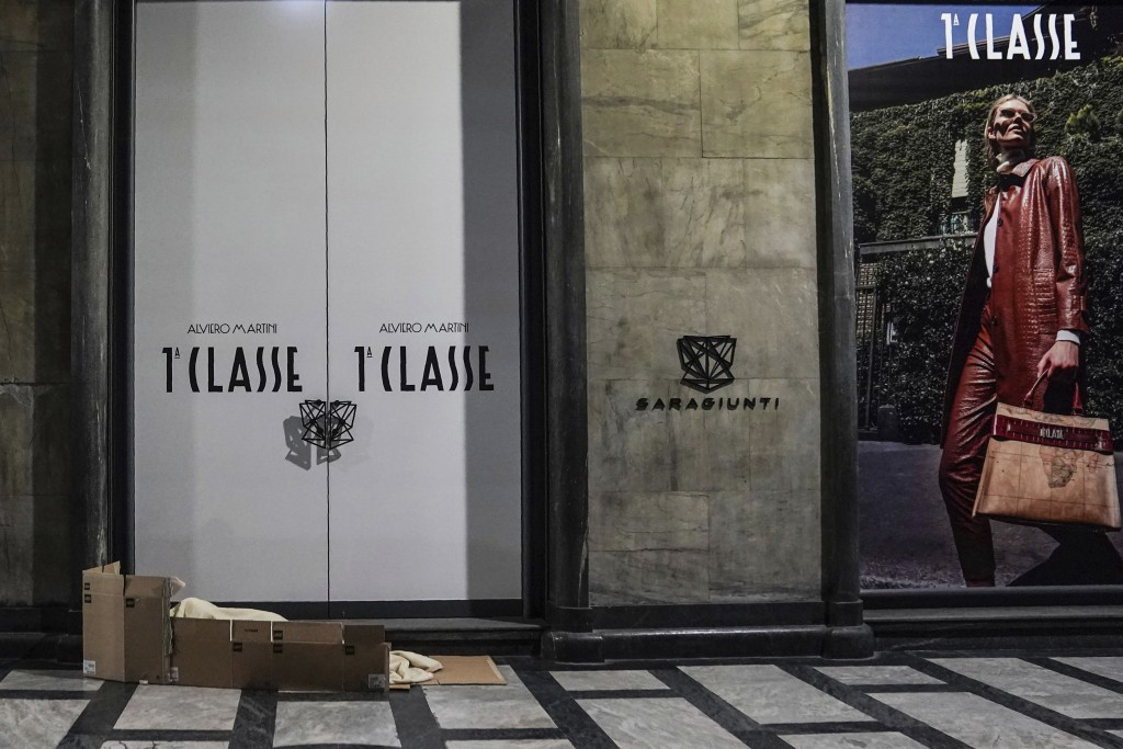 A homeless sleeps on the floor in front of a fashion store in downtown Milan, northern Italy, Friday, Nov. 27, 2020. Nowhere in Italy is poverty more ...