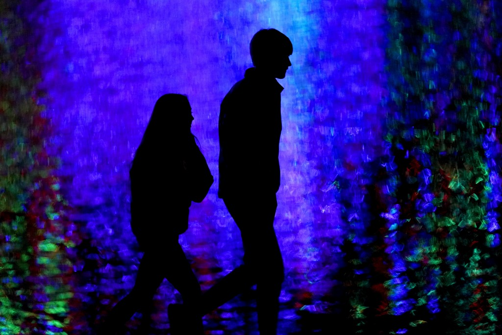 FILE - In this Dec. 16, 2020, file photo, people are silhouetted against Christmas lights reflected off a pond as they walk through a park in Lenexa, ...