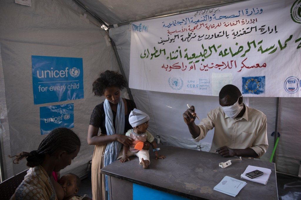 Women who fled the conflict in Ethiopia's Tigray region take shelter inside a UNICEF tent, as Filippo Grandi, U.N. High Commissioner for Refugees, vis...
