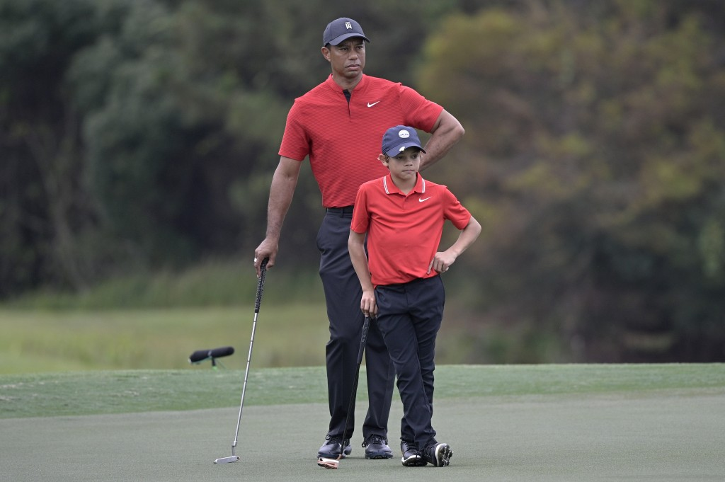 Tiger Woods and his son Charlie wait to putt on the 12th green during the final round of the PNC Championship golf tournament, Sunday, Dec. 20, 2020, ...
