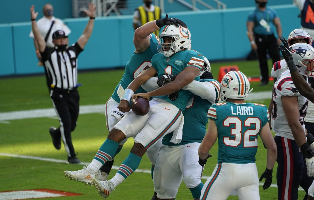 Miami Dolphins quarterback Tua Tagovailoa (1) celebrates his score against the New England Patriots during the second half of an NFL football game Sun...