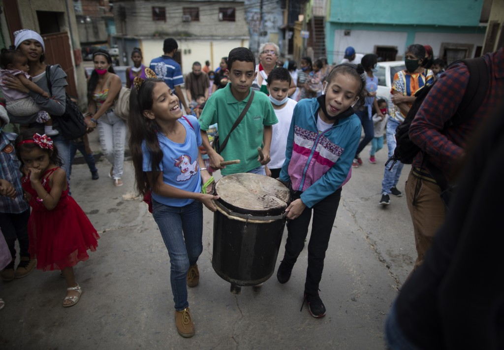 A boy plays the drum carried by friends as they go Christmas caroling in the La Vega area of Caracas, Venezuela, Saturday, Dec.19, 2020. (AP Photo/Ari...