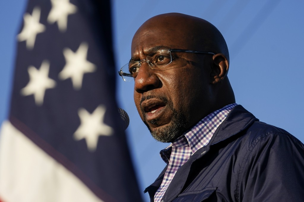 FILE - In this Nov. 15, 2020, file photo Raphael Warnock, a Democratic candidate for the U.S. Senate, speaks during a campaign rally in Marietta, Ga. ...