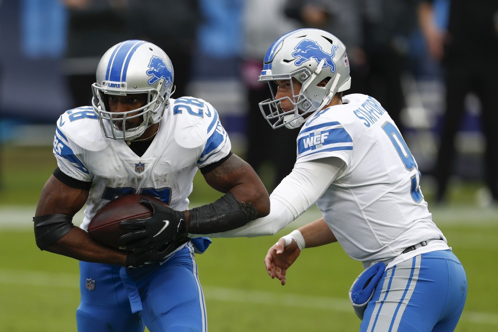 Detroit Lions quarterback Matthew Stafford hands off to the running back Adrian Peterson during the first half of an NFL football game Sunday, Dec. 20...