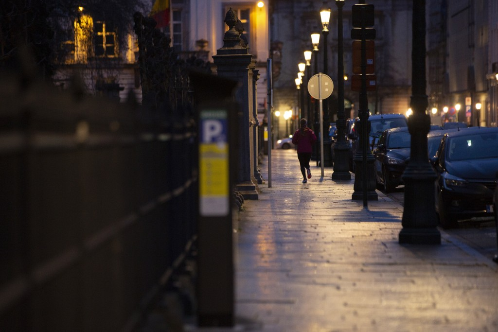 A woman jogs down a street in the early morning outside the UK ambassadors residence in Brussels, Monday, Dec. 21, 2020. The United Kingdom and the Eu...