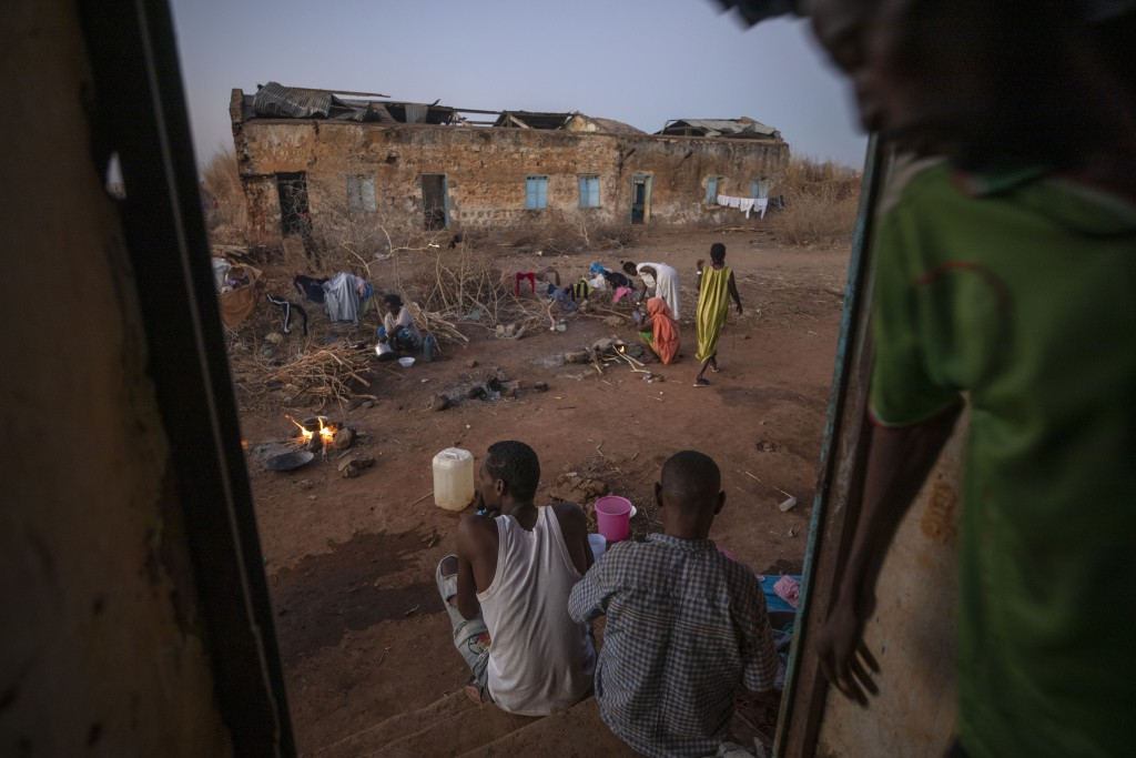 Tigrayan refugees who fled Ethiopia's conflict, prepare to cook their dinners in front of their temporary shelters, at Umm Rakouba refugee camp in Qad...