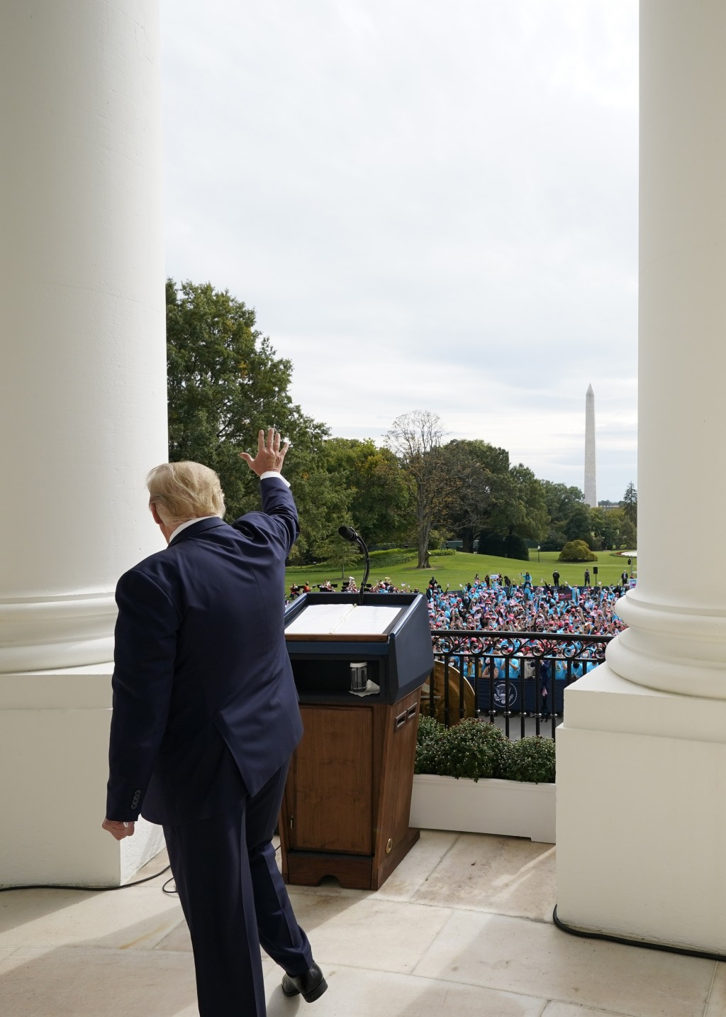 FILE - In this Oct. 10, 2020, file photo President Donald Trump waves from the Blue Room Balcony of the White House to a crowd of supporters in Washin...