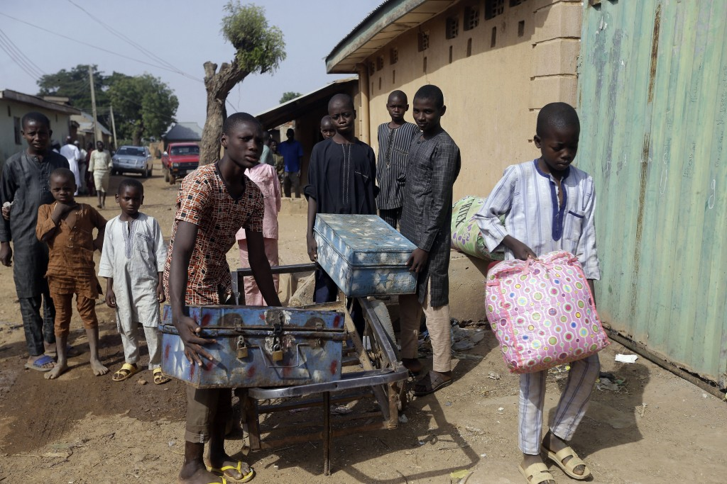 Habubakar Liti, left, Bello Ibrahim, centre, and Isah Nasir, recently released students, arrive back home carrying boxes containing their school belon...