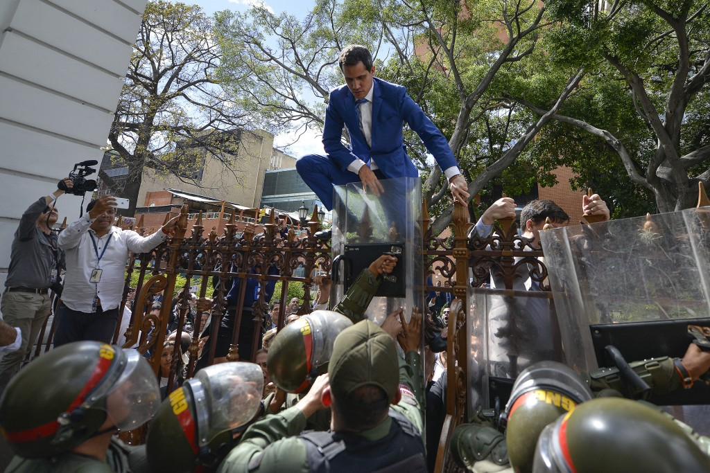 National Assembly President Juan Guaido, Venezuela's opposition leader, climbs the fence in a failed attempt to enter the Assembly compound as he and ...