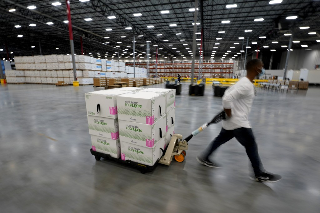 Boxes containing the Moderna COVID-19 vaccine are moved to the loading dock for shipping at the McKesson distribution center in Olive Branch, Miss., S...