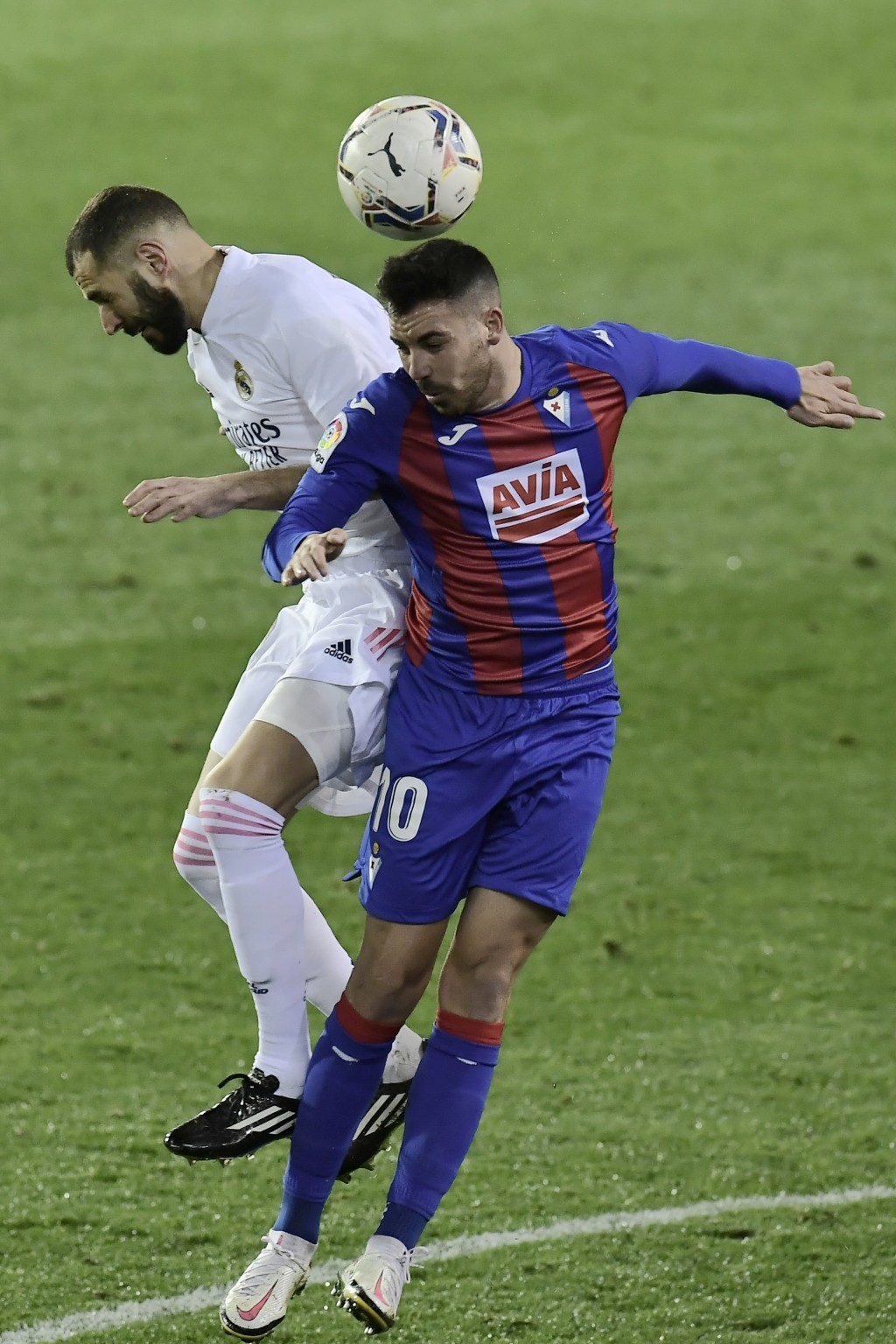 Real Madrid's Karim Benzema, left, jumps for the ball with Eibar's Edu Expositoduring the Spanish La Liga soccer match between Eibar and Real Madrid, ...