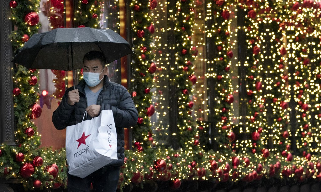 FILE - In this Nov. 30, 2020 file photo, a shopper walks by a holiday window display in New York. (AP Photo/Mark Lennihan, File)