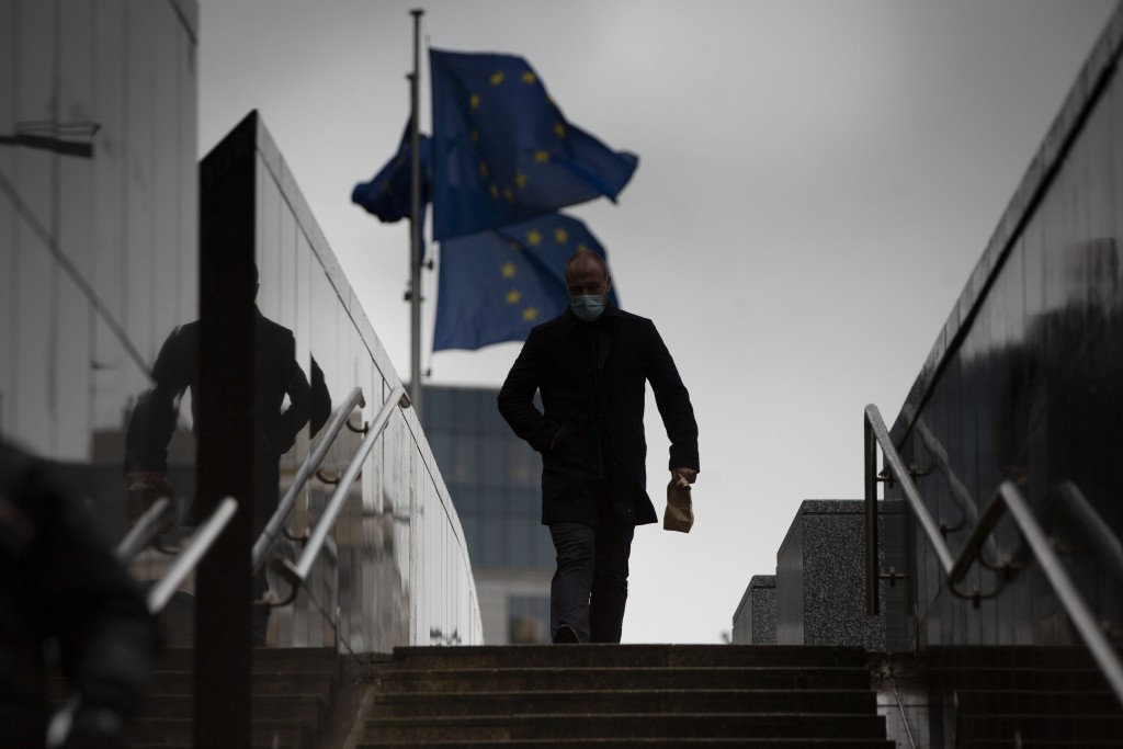 A man walks past EU flags flapping in the wind in front of the European Union headquarters in Brussels, Monday, Dec. 21, 2020. The United Kingdom and ...