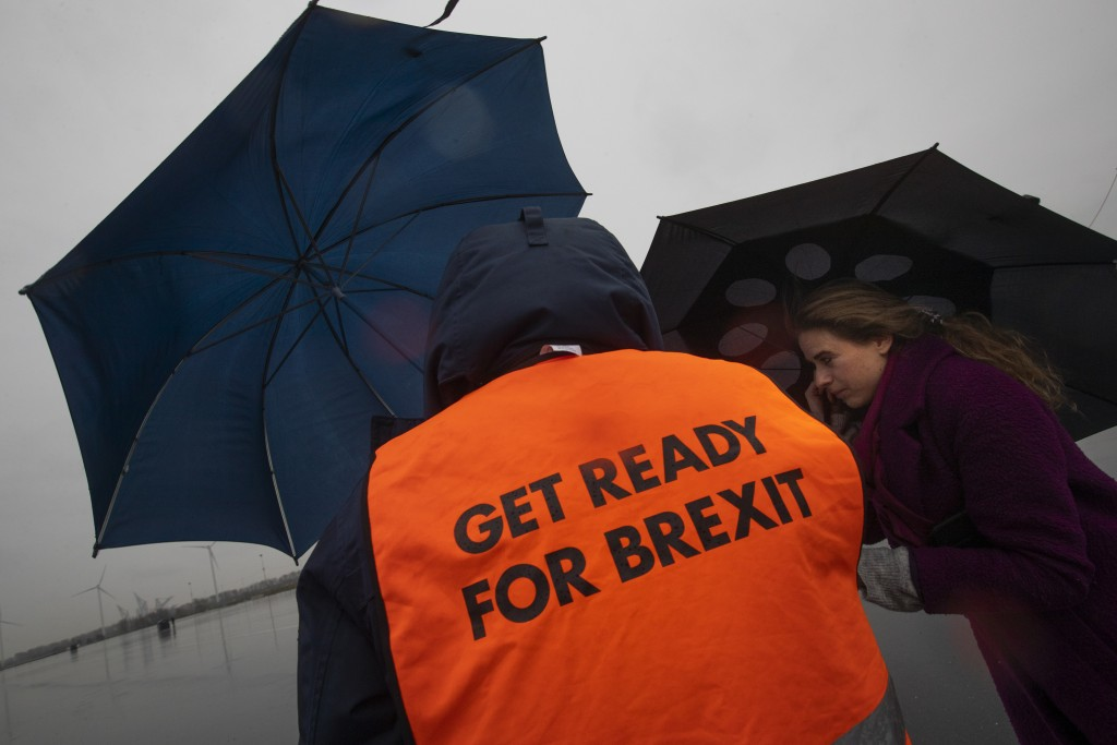 A spokesperson wears a safety vest during a press tour of an overflow parking lot for trucks after the Brexit transition period, in Hook of Holland, n...
