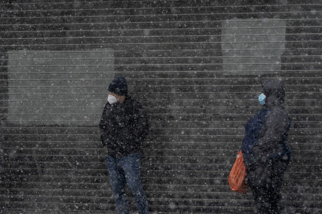 FILE - In this Dec. 17, 2020, file photo, people stand in line outside a COVID-19 testing site during a snowstorm in the Bronx borough of New York. (A...