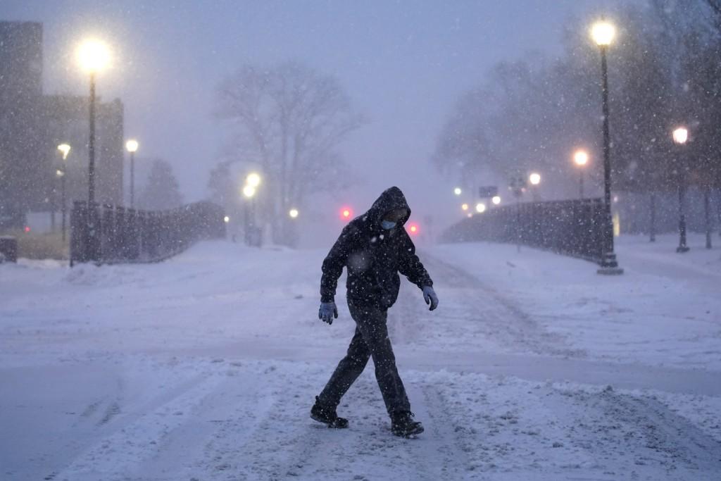 FILE - In this Dec. 16, 2020, file photo, a man walks through the Villanova University campus during a snow storm in Villanova, Pa. (AP Photo/Matt Slo...