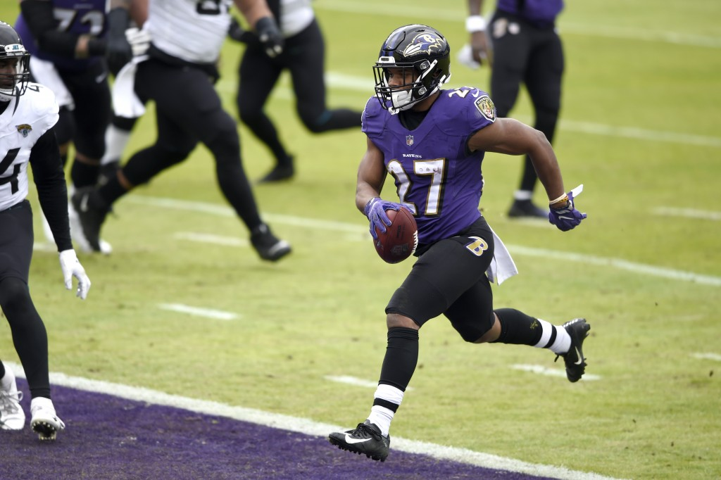 Baltimore Ravens running back J.K. Dobbins scores a touchdown on a run against the Jacksonville Jaguars during the first half of an NFL football game,...
