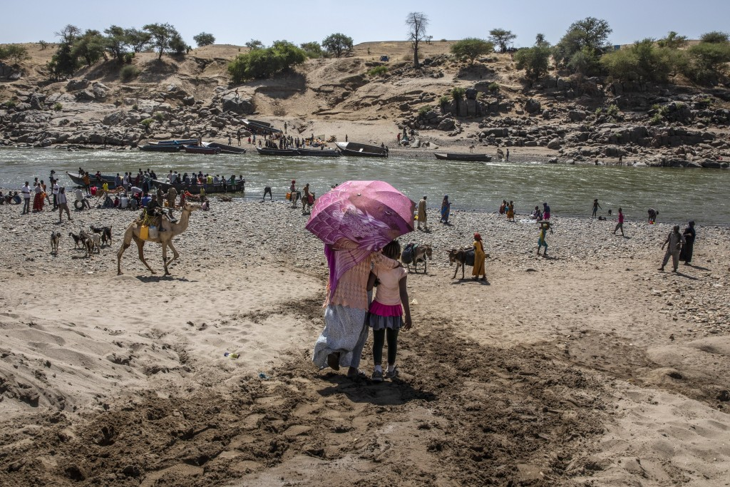 Refugees who fled the conflict in Ethiopia's Tigray region arrive on the banks of the Tekeze River on the Sudan-Ethiopia border, in Hamdayet, eastern ...