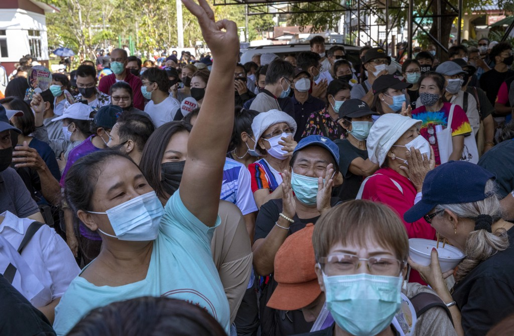 Pro-democracy protesters flash three-finger salute as their leader Arnon Nampha speaks from a makeshift stage outside Bang Khen Metropolitan Police St...