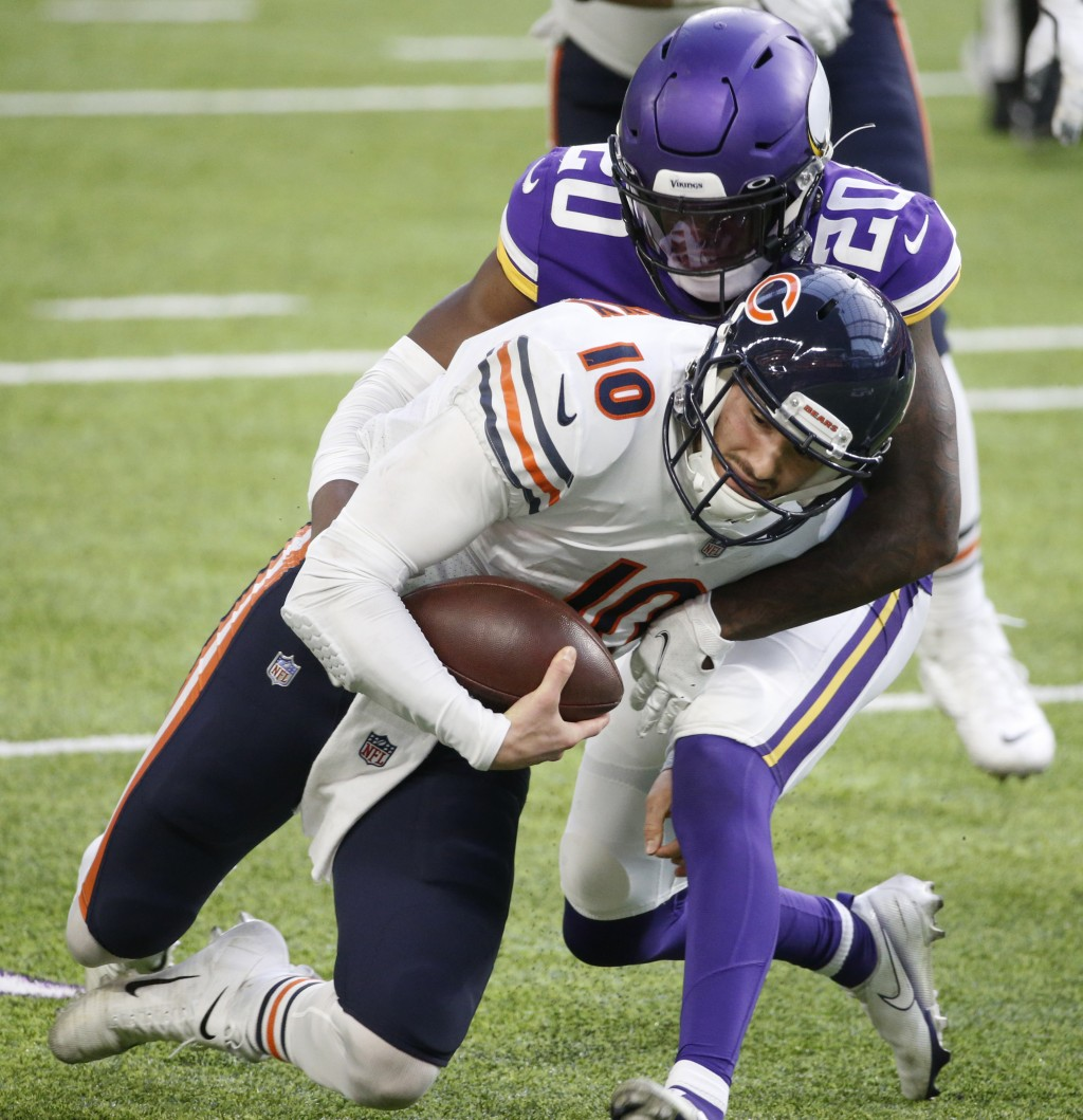 Chicago Bears quarterback Mitchell Trubisky (10 is tackled by Minnesota Vikings cornerback Jeff Gladney (20) during the second half of an NFL football...