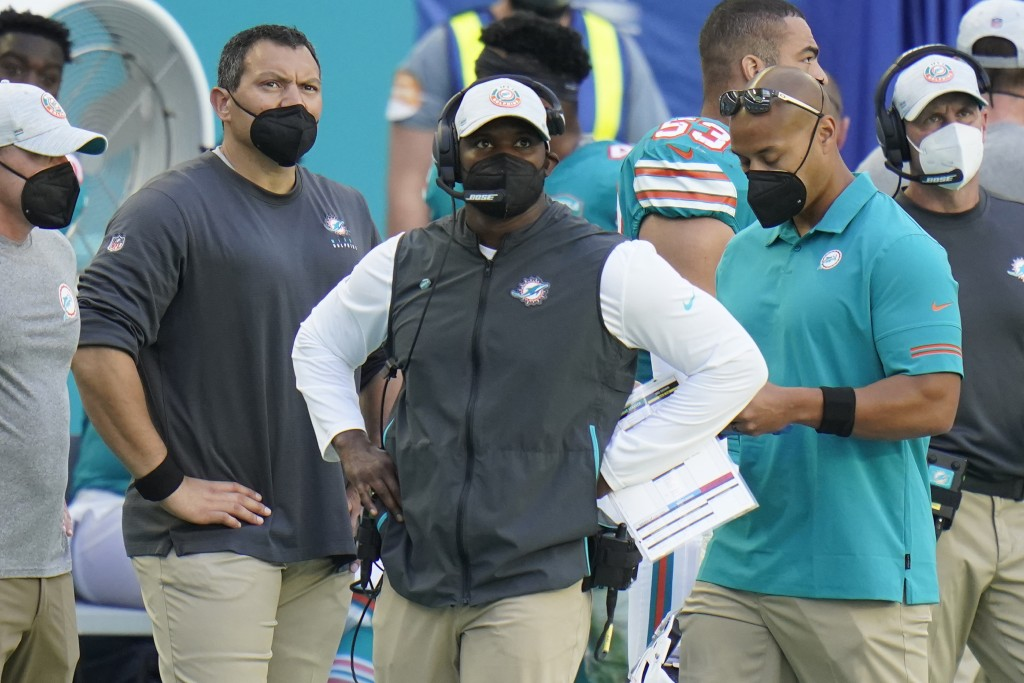 Miami Dolphins head coach Brian Flores, center, look up during the second half of an NFL football game against the New England Patriots, Sunday, Dec. ...