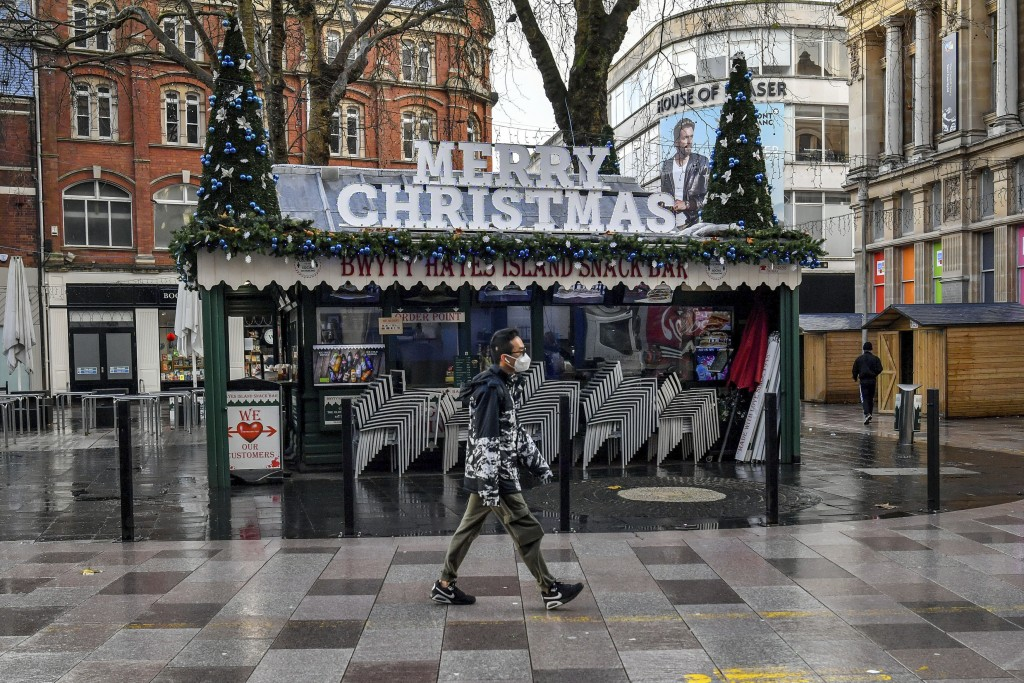 A person walks through Cardiff city centre, Sunday Dec. 20, 2020. In Wales, authorities said they decided to move up a lockdown planned for after Chri...