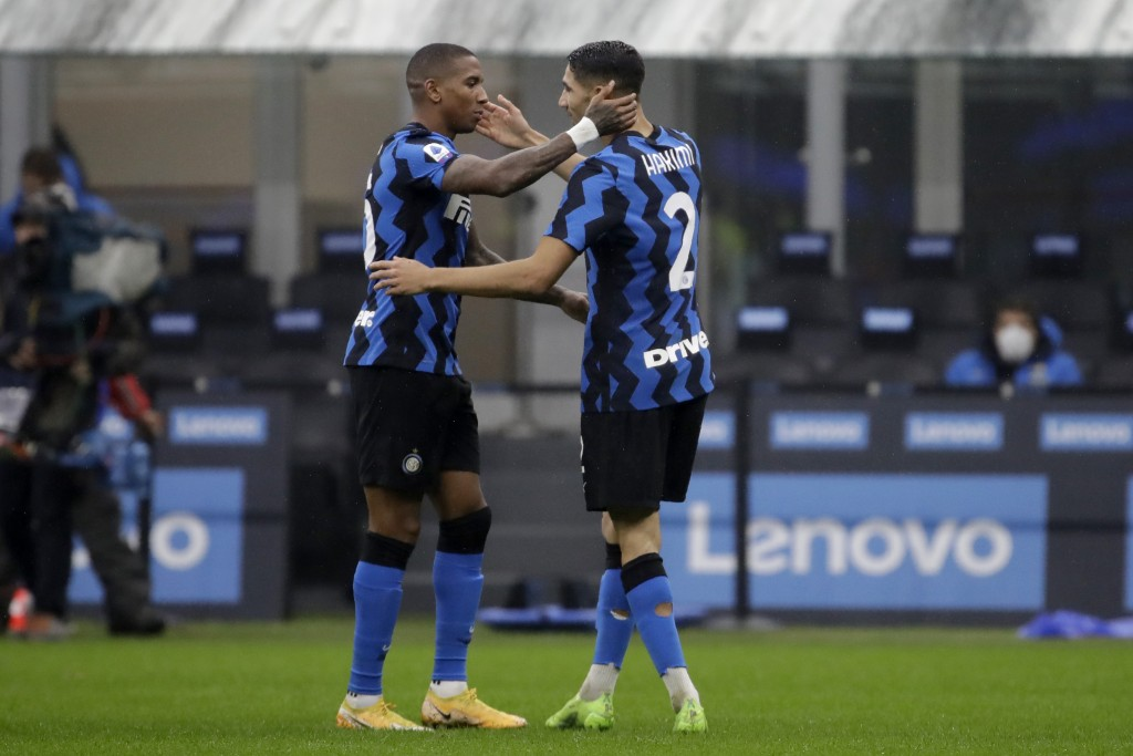 Inter Milan's Achraf Hakimi celebrates with his teammate Ashley Young, left, after scoring his side's opening goal during the Serie A soccer match bet...