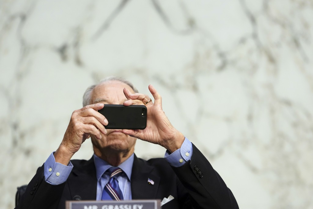 FILE - In this Monday, Oct. 12, 2020 file photo, Sen. Chuck Grassley, R-Iowa, uses his smartphone during a hearing on Capitol Hill in Washington. Rese...